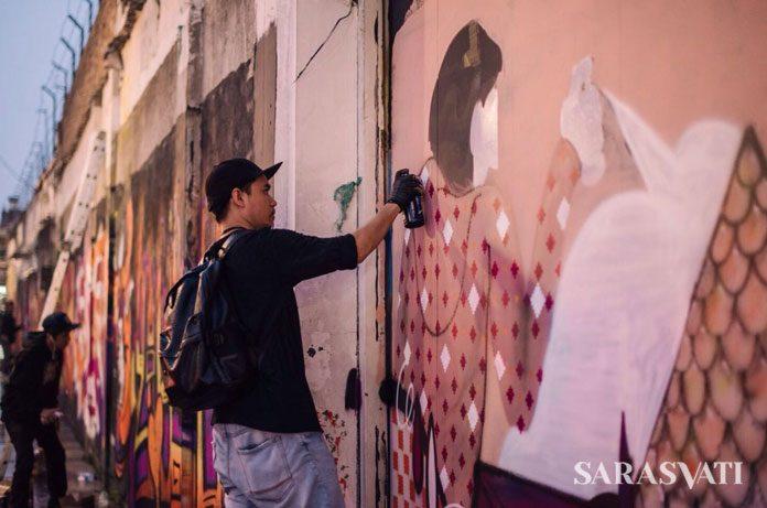 Salah satu street artist sedang berkarya di tembok Jalan Jend. Sudirman di seberang Roemah Seni Sarasvati