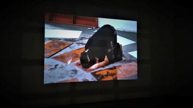 Proses pengerjaan karya Tisna dengan gerakan sujud ditampilkan dalam video dokumenter (Foto: Dhamarista Intan)