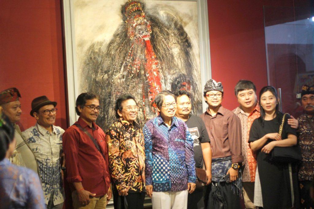Para penginisiasi pameran berfoto di depan lukisan Rangda.
